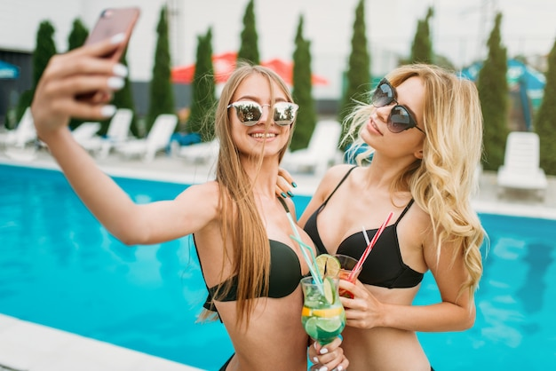 Zwei sexy girls machen selfie in der nähe des schwimmbades