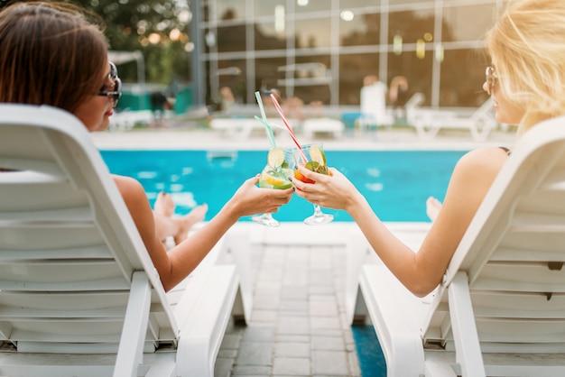 Zwei sexy mädchen entspannen sich mit cocktails auf liegestühlen in der nähe des schwimmbades. schlanke frauen sitzen am pool, urlaub im resort