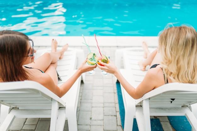 Zwei sexy mädchen entspannen sich mit cocktails auf liegestühlen