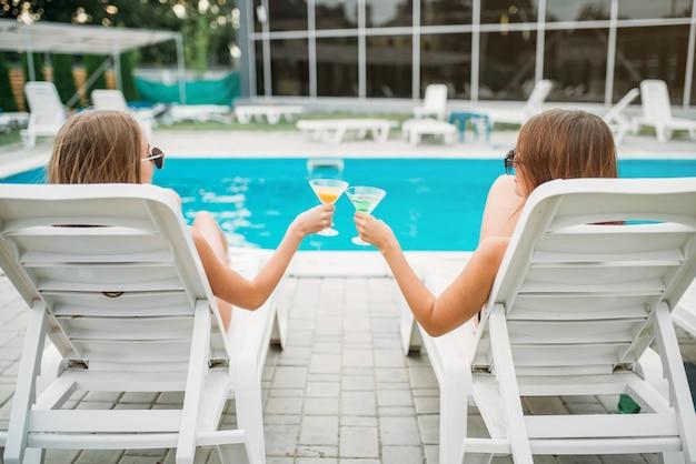 Zwei sexy mädchen mit cocktails liegen auf liegestühlen in der nähe des schwimmbades. schlanke frauen sitzen am pool, urlaub im resort