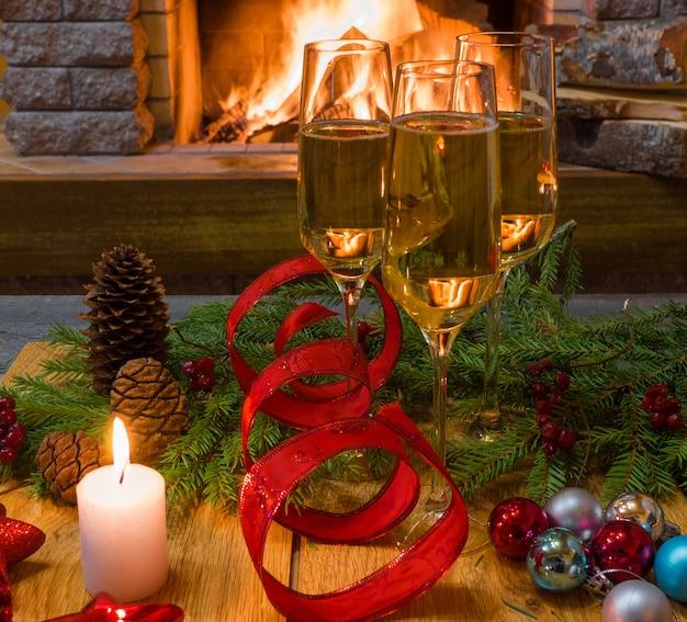 Zwei shampagne-gläser, weihnachtsdekorationen und kerze gegen gemütlichen kamin.