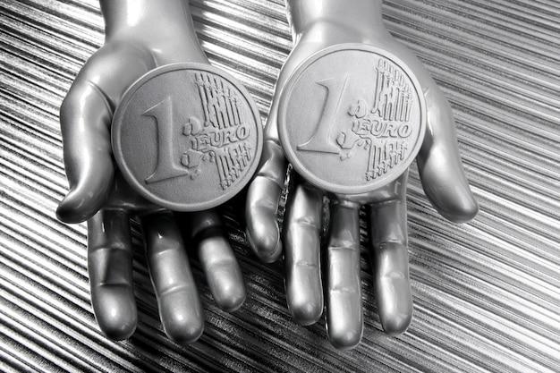 Zwei silberne euromünzen in den futuristischen roboterhänden