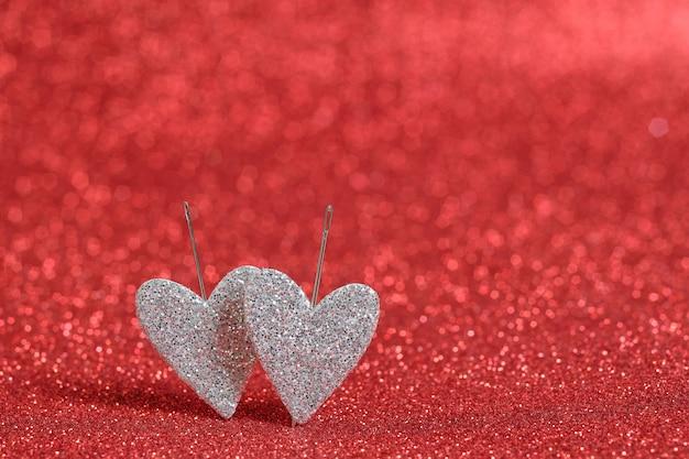 Zwei silberne herzen an einer roten bokehwand. herzen werden mit nadeln an die wand gestochen. bild für valentinstag und hochzeit. bokeh rote farbe wand.