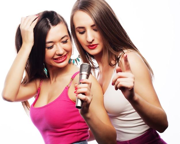 Zwei sinnliche mädchen singen mit mikrofon, isoliert auf weiß
