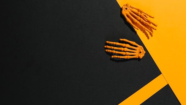 Zwei skeletthände auf orange papier