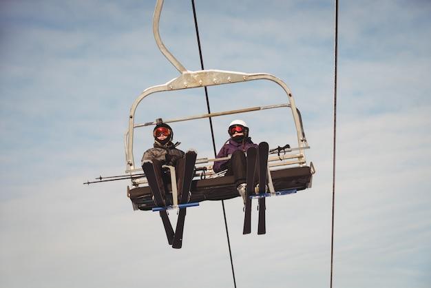 Zwei skifahrer, die im skilift im skigebiet reisen
