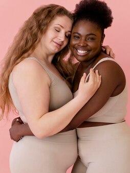 Zwei smiley-frauen, die posieren, während sie einen körperformer tragen