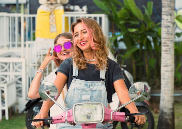 Zwei smiley-freundinnen draußen auf dem roller