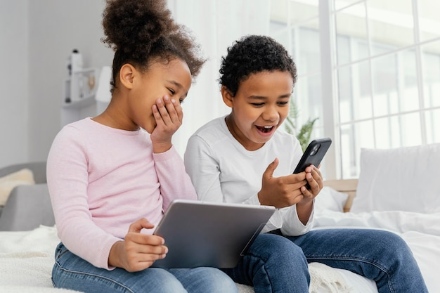 Zwei smiley-geschwister zu hause spielen zusammen auf tablet und smartphone