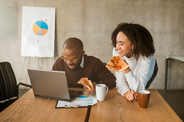 Zwei smiley-kollegen, die während einer büro-besprechungspause pizza essen
