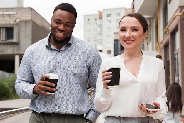 Zwei smiley-kollegen, die zusammen bei der arbeit kaffee trinken