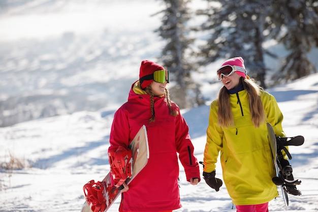 Zwei snowboarder laufen und unterhalten sich auf einem schneebedeckten berg