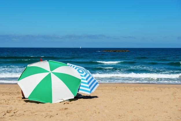 Zwei sonnenschirme am strand, blauer himmel