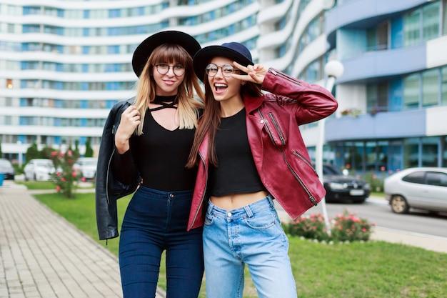 Zwei sorglos lächelnde frauen, die auf der modernen stadt aufwerfen. tragen von wollmütze, lederjacke und jeans.