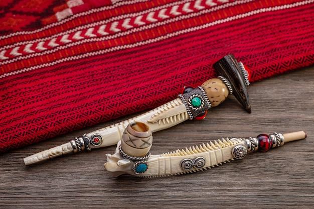 Zwei souvenir-tabakpfeifen und rotes plaid der amerikanischen ureinwohner. kopierraum, studioaufnahme.