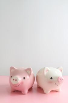 Zwei sparschwein auf rosa tabelle mit weißem hintergrund. ein sparsames geld für das zukünftige investitionskonzept.