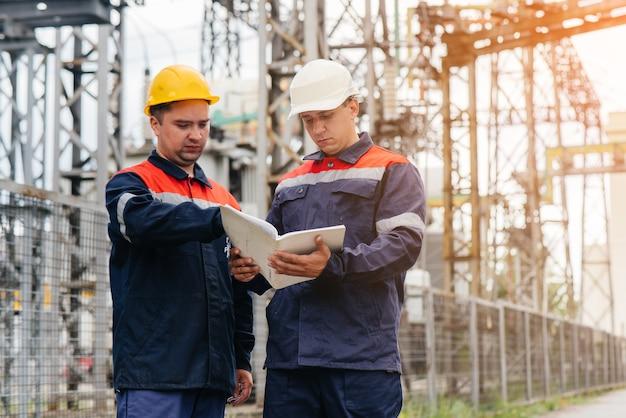 Zwei spezialisierte umspannwerkingenieure inspizieren abends moderne hochspannungsgeräte. energie. industrie.