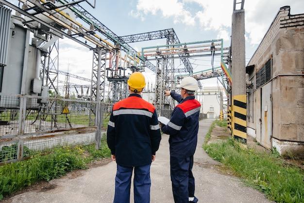 Zwei spezialisierte umspannwerkingenieure inspizieren moderne hochspannungsgeräte. energie. industrie.