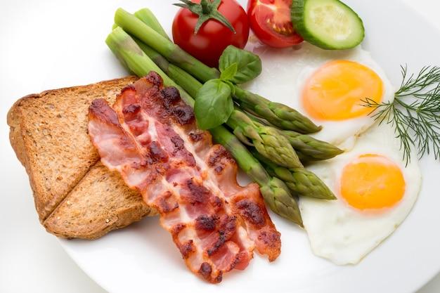 Zwei spiegeleier und speck für ein gesundes frühstück. selektiver fokus