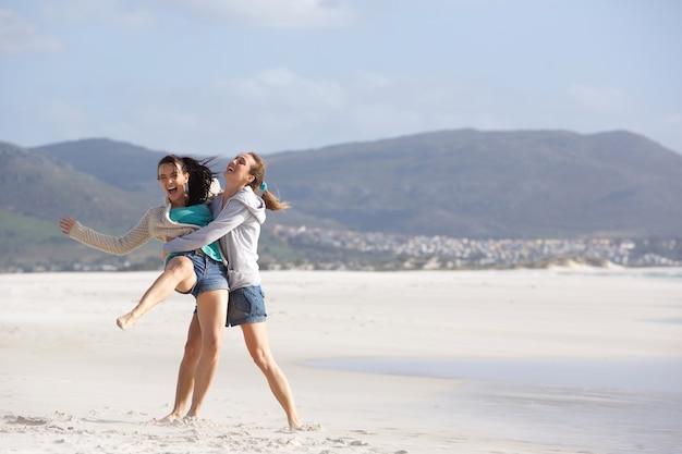Zwei spielerische freundinnen, die eine gute zeit am strand haben