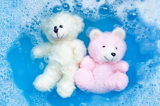 Zwei spielzeugbären in waschmittelwasserlösung einweichen