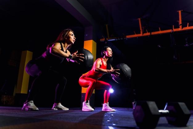 Zwei sportfrauen, die hockenübungen mit eignungsball tun. frau, die mit medizinball an der turnhalle trainiert und ausdehnt
