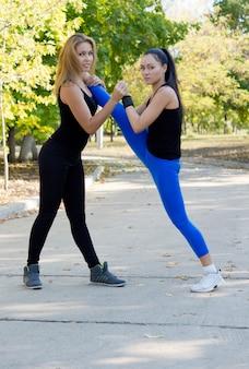 Zwei sportlerinnen, die zusammen trainieren, machen dehnübungen mit gleichgewichtskontrolle, während sie in einem park trainieren