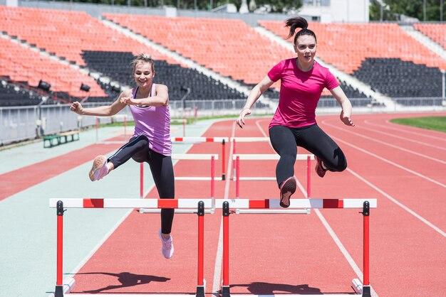 Zwei sportlerinnen springen über ein hindernis. laufen mit hürden. aktiver lebensstil