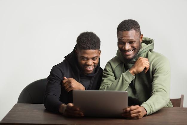 Zwei sportliche afrikanische männer in trainingsanzügen auf einem weißen hintergrund an einem tisch mit einem laptop