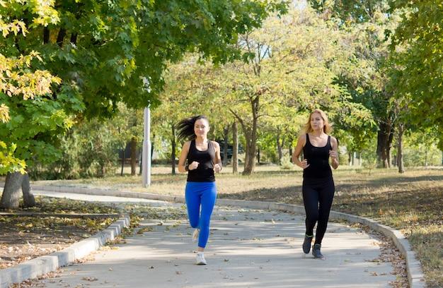 Zwei sportliche attraktive frauen, die in einem park zusammen in einem gesundheits- und fitnesskonzept joggen