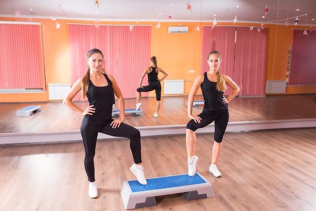 Zwei sportliche junge frauen treten zusammen auf aerobic-schritten in der turnhalle, während sie vor der kamera posieren.