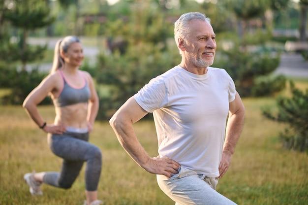 Zwei sportliche reife erwachsene trainieren im park