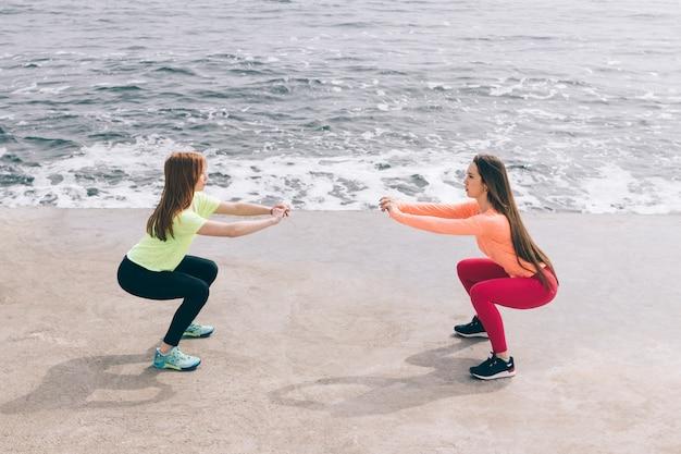 Zwei sportmädchen machen kniebeugen am strand.