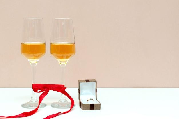 Zwei sprudelnde champagnergläser und schachtel mit goldenem ring auf weiß mit kopienraum, valentinstag, liebe, vorschlagskonzept.