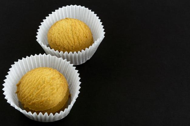 Zwei stapel kekse in papierkörben auf schwarzem papier