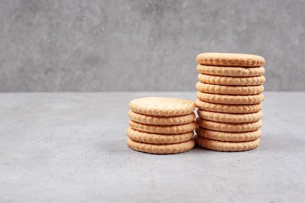 Zwei stapel knuspriger kekse auf marmorhintergrund. hochwertiges foto