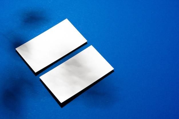 Zwei stapel leere visitenkarten auf blauem hintergrund schließen