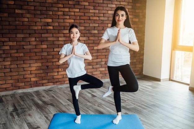 Zwei starke mädchen des brunette in der morgenzeit, yoga tuend. mit sonnenlicht.