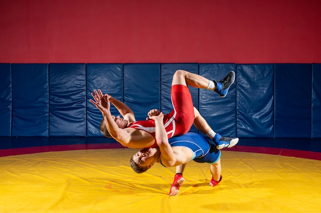 Zwei starke männer in blauen und roten wrestling-strumpfhosen ringen und machen ein suplexes wrestling auf einem gelben wrestling-teppich im fitnessstudio. wrestler kämpfen.