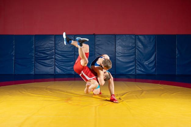 Zwei starke männer in blauen und roten wrestling-strumpfhosen ringen und machen ein suplexes wrestling
