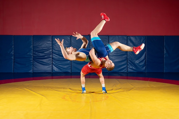 Zwei starke wrestler in blauen und roten wrestling-strumpfhosen machen im fitnessstudio einen hüftwurf auf einem gelben wrestling-teppich.