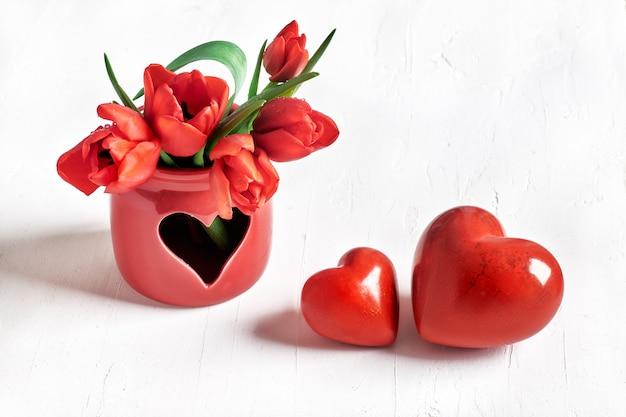 Zwei steinherzen und bündel rote tulpen auf weiß