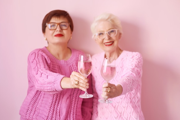 Zwei stilvolle ältere frauen in rosa pullovern mit roséweingläsern auf rosa hintergrund