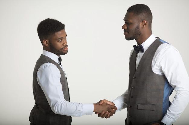 Zwei stilvolle afrikanische männer in anzügen auf weißer wand mit händedruck