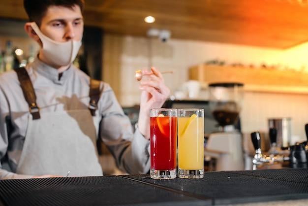 Zwei stilvolle barkeeper in masken und uniformen während der pandemie, die cocktails zubereiten. die arbeit von restaurants und cafés während der pandemie. Premium Fotos