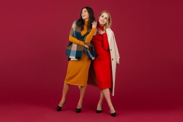 Zwei stilvolle frauen im herbst wintermode kleid und mantel posieren isoliert auf roter wand