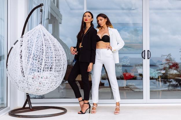 Zwei stilvolle frauen in schwarzen und weißen anzügen und absätzen stehen vor der villa an der wand der glaswand