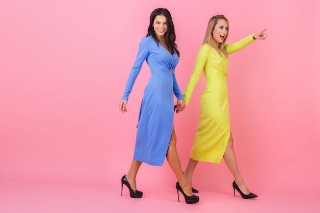 Zwei stilvolle lächelnde attraktive frauen, die zusammen in voller höhe auf rosa wand in stilvollen bunten kleidern der blauen und gelben farbe, frühlingsmodetrend, zeigefinger gehen