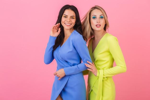 Zwei stilvolle lächelnde attraktive freundinnen, die auf rosa wand in stilvollen bunten kleidern der blauen und gelben farbe, frühlingsmodetrend aufwerfen