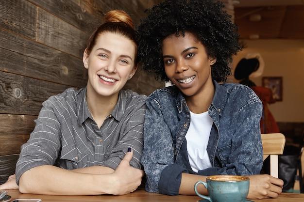 Zwei stilvolle lesben, die zusammen beim mittagessen im café kaffee trinken
